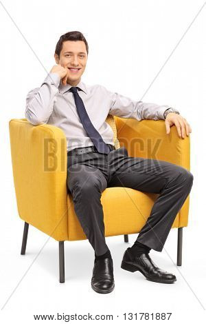 Vertical shot of a confident young businessman sitting in a comfortable yellow armchair isolated on white background