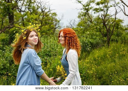 Best friends forever. Friends meet in the park. BFF. A girl holding a bouquet of wildflowers. A wreath of flowers on the head of the girl.