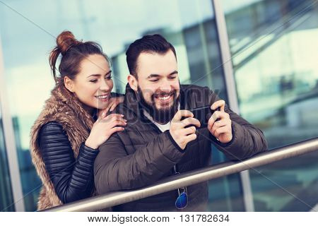 Picture of young couple hanging out in city and taking selfie