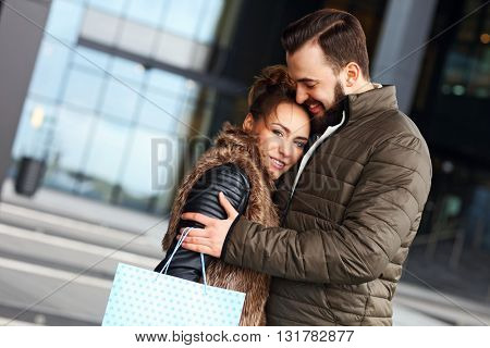 Picture of happy couple hugging while shopping