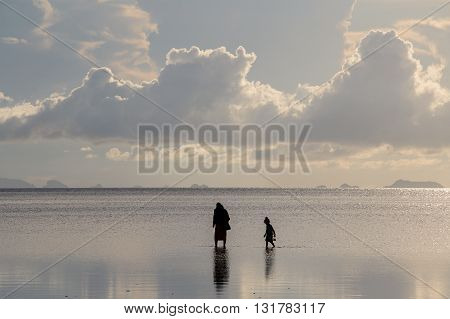 Silhouette woman and child clams harvested during sunset on the island of Koh Phangan Thailand