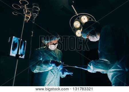 Surgeons team working with Monitoring of patient in surgical operating room. breast augmentation.