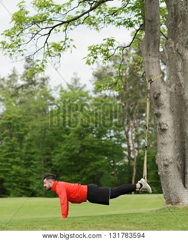 Picture of sport man training in park. Stretching after or before jogging. Handsome man in red jacket doing sport.