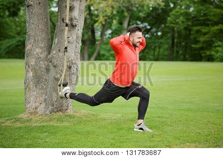Sport man exercising with suspension trainer sling in city Park under summer trees for sport fitness. Happy man in red jacket.