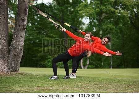 Young attractive woman and man do suspension training with fitness straps outdoors in nature. Group of people training simultaneously.