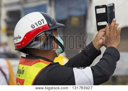 PHUKET THAILAND - OCT 18 2015:Thai police photographs on the smartphone procession during the Vegetarian Festival at Phuket Town. Festival is a famous annual also known as Nine Emperor Gods