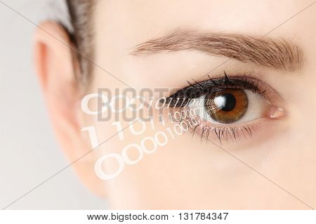 Close-up of eye of woman with binary code