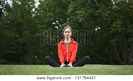 Pretty woman doing yoga exercises in green park or forest. Happy lady in red jacket sitting on green grass and looking at camera.