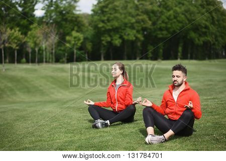 Handsome man and beautiful woman doing yoga in green park or forest. Healthy lifestyle and relaxation concepts.