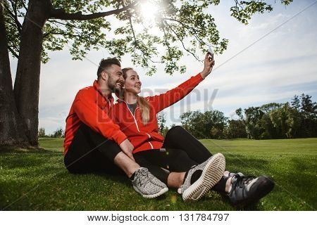 Sport man and woman making selfies in green park or forest while resting and relaxing after hard-working day. Fitness, sportrs and lifestyle concepts.