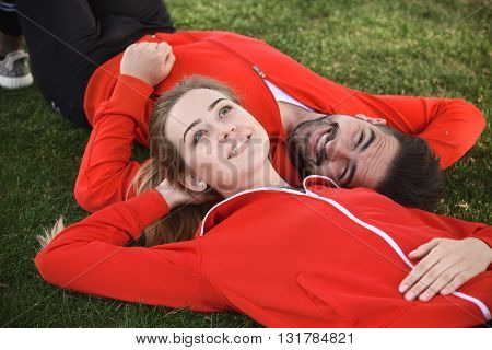 Portrait of sport man and woman in red jackets resting and relaxing in green park. Happy couple lying face to face on green grass.