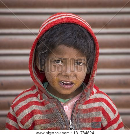 LEH INDIA - JUNE 29 2015: Unidentified poor Indian beggar boy on street in Ladakh. Children of the early ages are often brought to the begging profession.