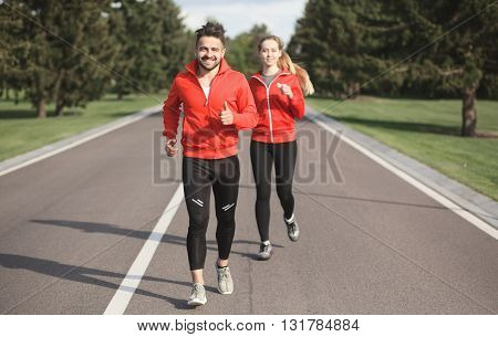 Sport man and woman jogging along road. Beautiful couple in red jackets training and looking at camera. Fitness concept.