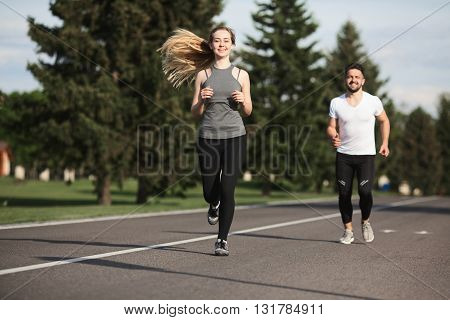 Closeup portrait of sport woman jogging along road with her partner or boyfriend running on background. Fitness, sport and lifestyle concepts.