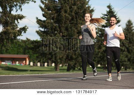 Young woman and man running along street or road. Happy couple doing sport and thinking about something positive.