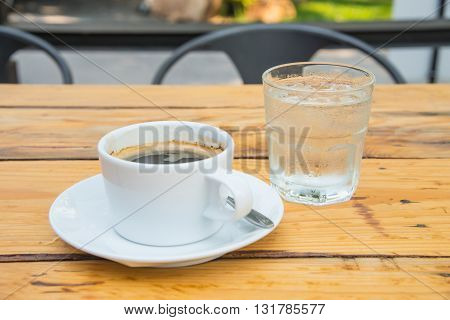 White coffee cupGlass water placed on wooden floor.Focus coffee cup.