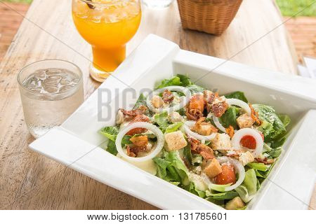 Caesar salad in White plateOrange juiceGlass of water placed on wooden table.