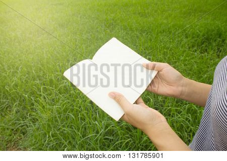 the notebook in hand with grass background