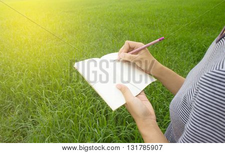 Pencil and notebook in hand with grass background