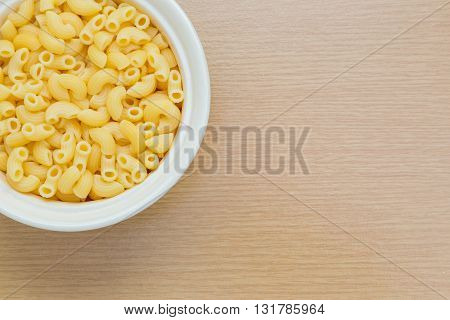 Macaroni in white bowl on wooden table compose to the side to leave room for copy space