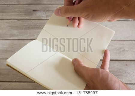 Pencil and notebook in hand with wood background