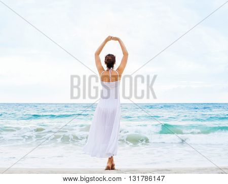 Rear view of beautiful, young lady enjoying the scene of wavy ocean.