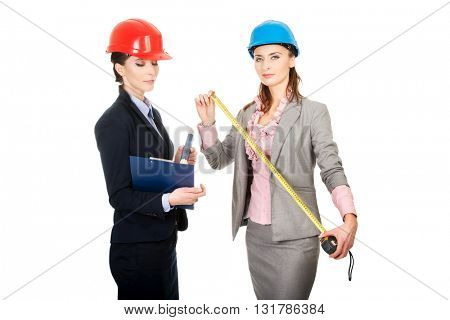 Two engineer businesswomen with tape measure.