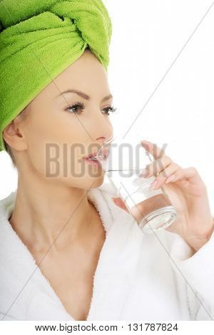 Woman in bathrobe drinks water.