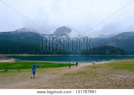 ZABLJAK MONTENEGRO - SEPTEMBER 20 2015: Unidentified tourists visit Black Lake in Durmitor National Park on rainy day Montenegro