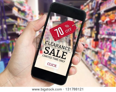 Hand holding mobile phone with sale tag and supermarket blur background.
