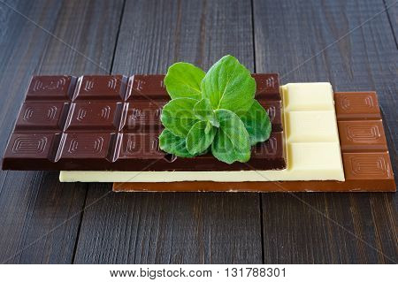 White milk black chocolates with mint on dark wooden boards