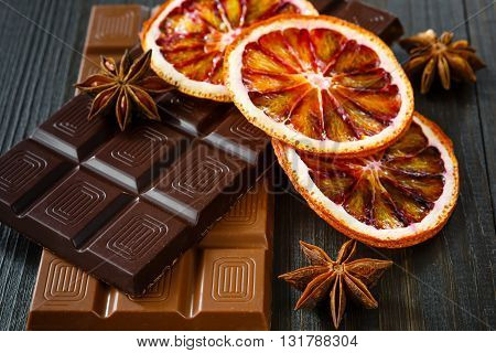 Milk black chocolates with dry oranges on dark wooden boards