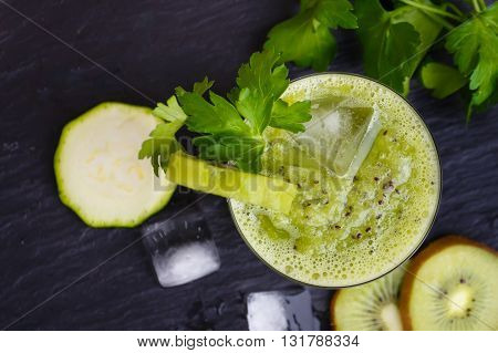 Green smoothie with kiwi baby spinach and parsley. Top view.