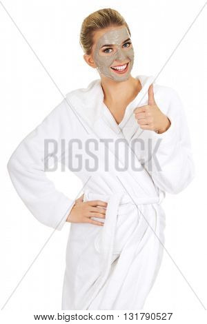 Young woman with facial mask shows OK sign.