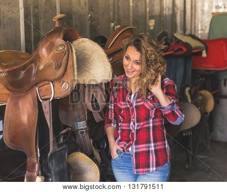 Pretty blonde girl with red shirt posing in equestrian context