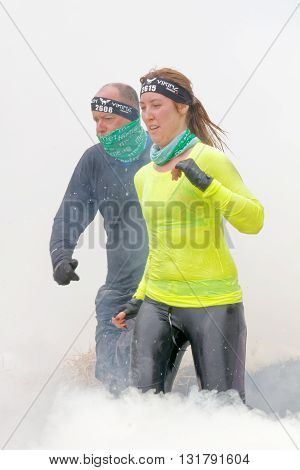 STOCKHOLM SWEDEN - MAY 14 2016: Woman in yellow shirt and man running through fire and smoke in the obstacle race Tough Viking Event in Sweden April 14 2016
