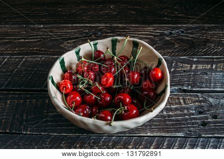 red cherries in a ceramic bowl ceramic bowl in the green bar red cherries red cherries on a brown background bowl with cherries
