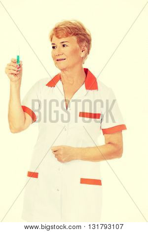 Smile elderly female doctor or nurse holds syringe