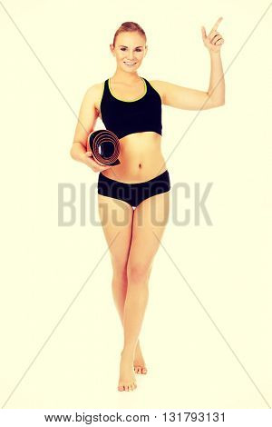 Young athletic woman holding mat and pointing for something