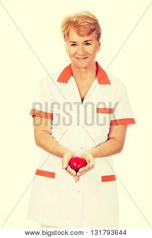 Smile elderly doctor or nurse holding red toy heart