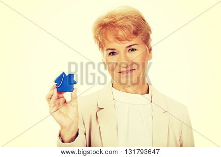 Smile elderly woman holding blue key pendant