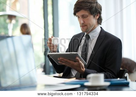 Business man with tablet computer in cafe
