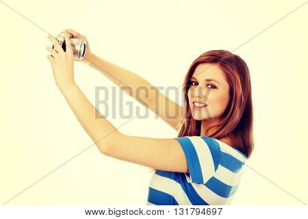 Happy teenage woman taking selfie with classic slr camera