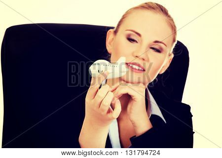 Business woman sitting behind the desk and holding a toy plane