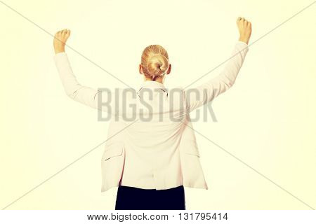 Back view of happy business woman with arms up