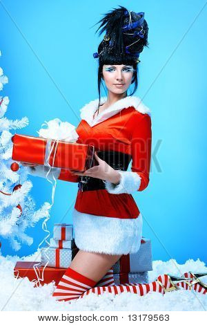 Beautiful young woman in Santa Claus clothes holding a present over Christmas background.