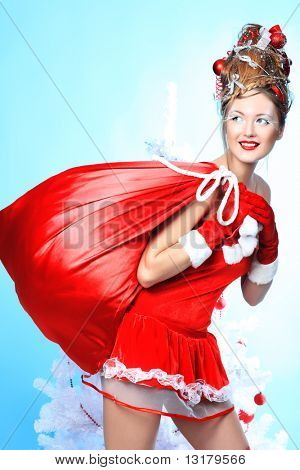 Beautiful young woman in Santa Claus clothes holding presents over Christmas background.