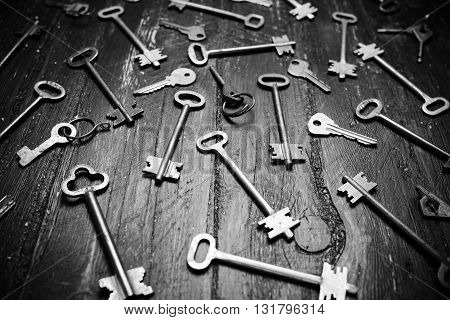Some door keys on old wooden surface, safety and security concept background. Black and white photo.