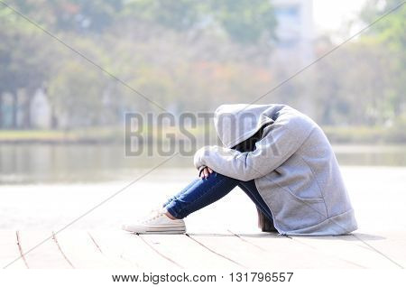 Sad woman hugging her knee and sitting near river