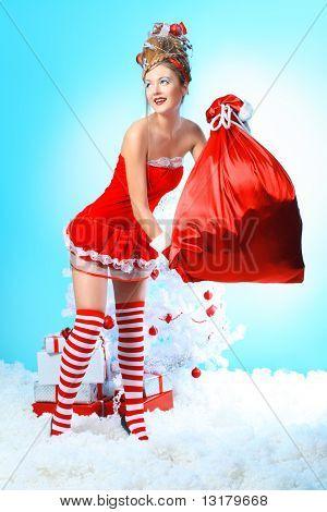 Schöne junge Frau in Santa Claus Kleidung holding präsentiert über Weihnachten Hintergrund.